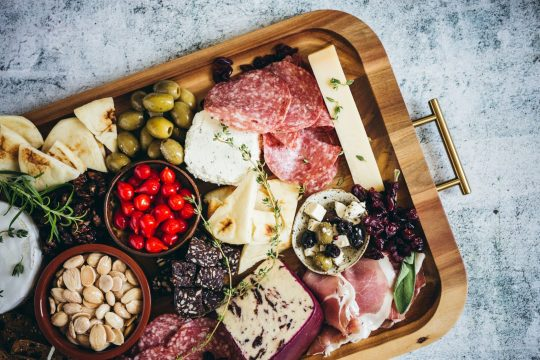 Charcuterie board with olives, pita, cheese, meats and ntus