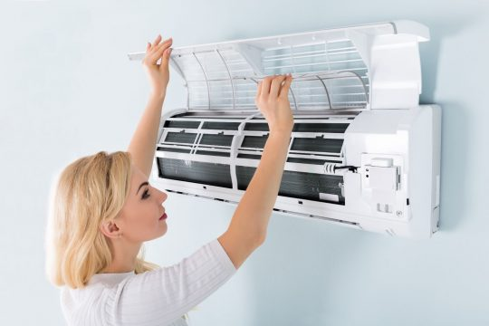 Woman checking her a/c unit's air filter