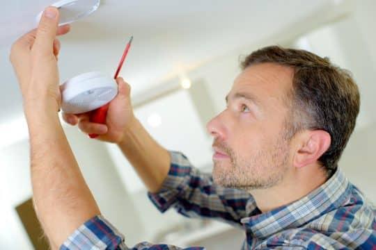 Man installing a smoke and carbon monoxide detector
