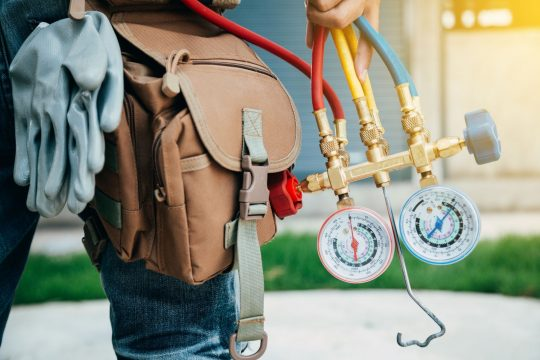 HVAC technician getting ready to walk into a house