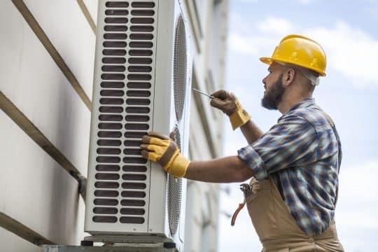 HVAC technician fixing an a/c unit outside