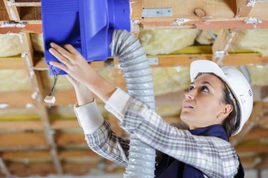 Female  HVAC technician installing a system in the attic