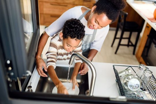 Mom and son washing dishes together