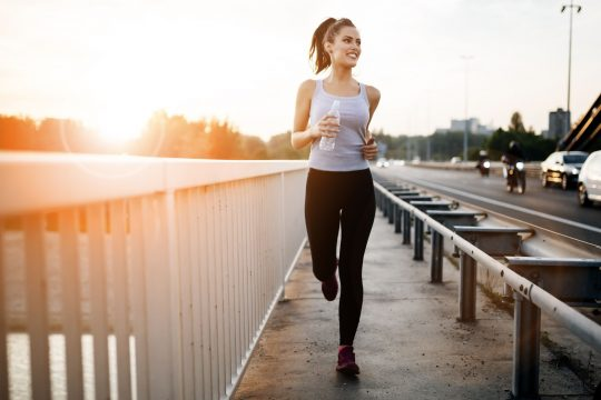 Woman smiling as she jogs with a water bottle in hand