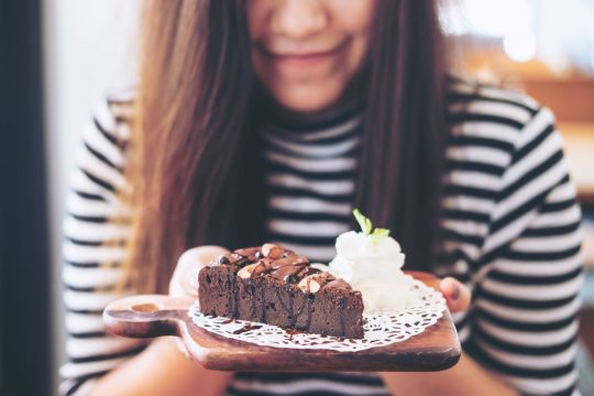 Woman smiling as she holds a chocolate brownie and scoop of vanilla ice cream to the camera