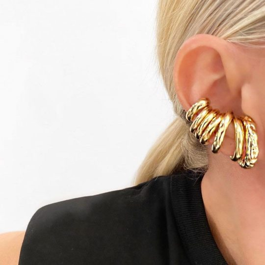 Woman with a stack of thick gold ear cuffs