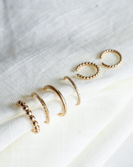 A handful of gold ear cuffs on a white cloth