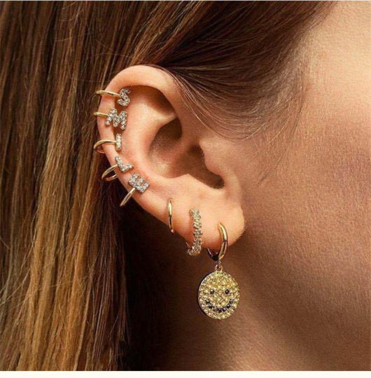 Woman with the word SMILE spelled out in ear cuffs
