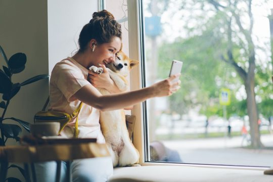 Woman taking a selfie with her corgi