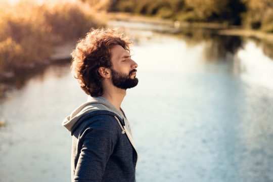 Bearded man breathing in front of a lake