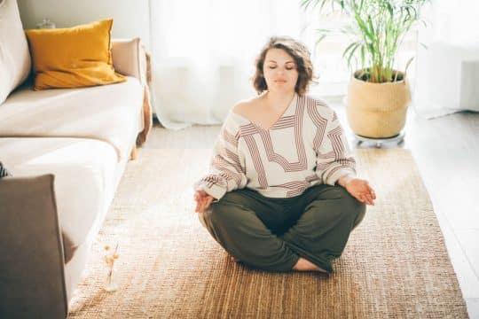 Woman sitting on her living room floor, breathing