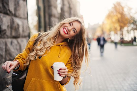 Woman is smiling at the camera with coffee in her hands