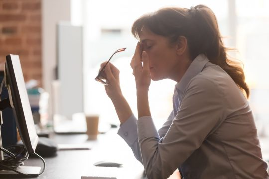 Woman with a migraine at work