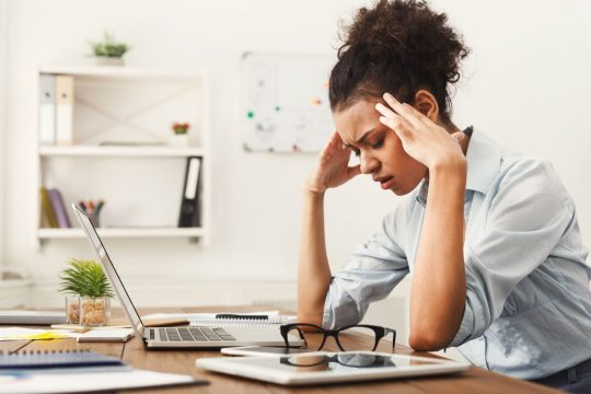 Woman holding her head in her hands at her desk