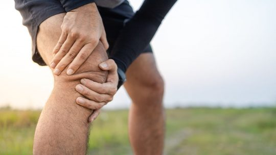 Man grabbing his knee in pain while on a run outside