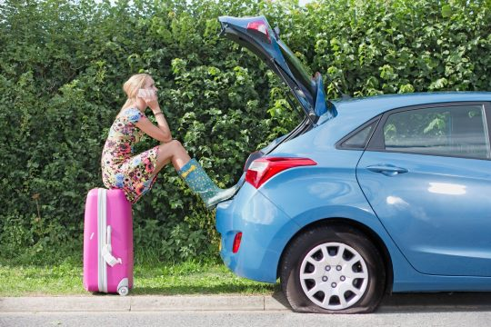 Woman sitting on her pink suitcase with her trunk open. Her blue car has a flat tire.