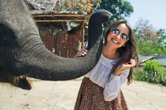 Woman smiling and posing for a picture while she holds an elephant's trunk