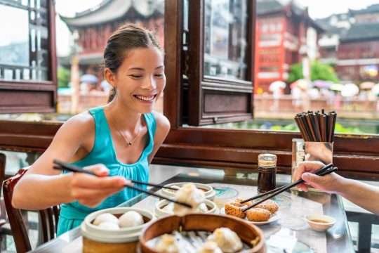 Woman sitting at a restaurant in china, eating
