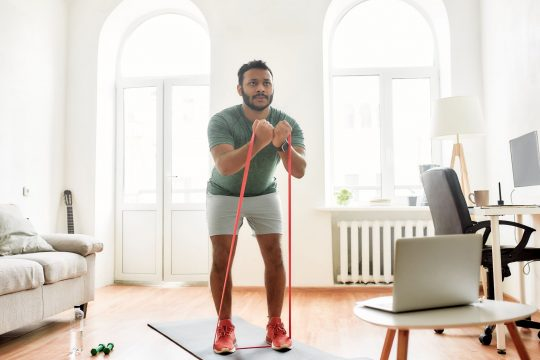 Man pulling up on a resistance band in his living room