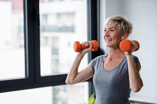 Woman holding hand weights by her ears, smiling