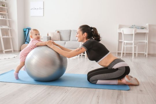 Woman and her baby playing with a Gaiam balance ball