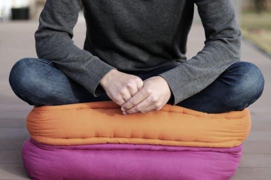 Man sitting on an orange and fuchsia colored cushions