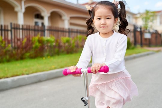 Young girl with pig tails riding a pink scooter, looking at the camera with a slight smile