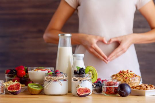 Woman making a heart with her hands over her stomach. There is a table with yogurt and fresh fruits and veggies on a table in front of her
