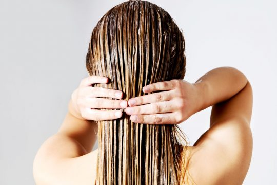 Woman running her fingers over her hair after putting a clay hair mask in