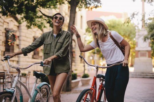 Two woman walking their bikes while they laugh and have a good time