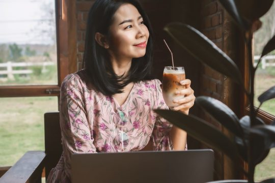 Woman holding a glass of cold brew, smiling and looking out the window