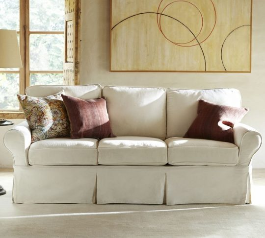 Couch with white Pottery Barn sofa cover, two muted red throw pillows, a floral throw pillow and a modern art piece in the background