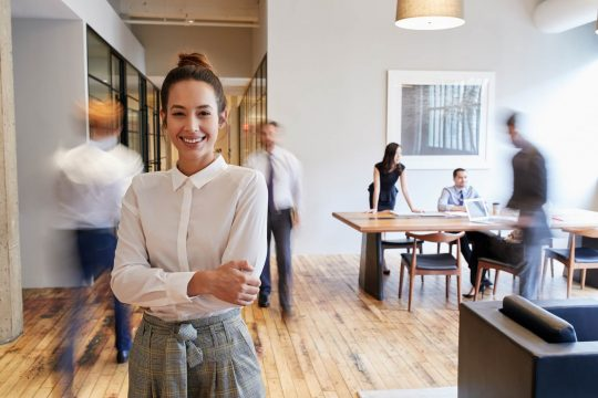 Woman in office smiling at the camera with people hustling and bustling behind her