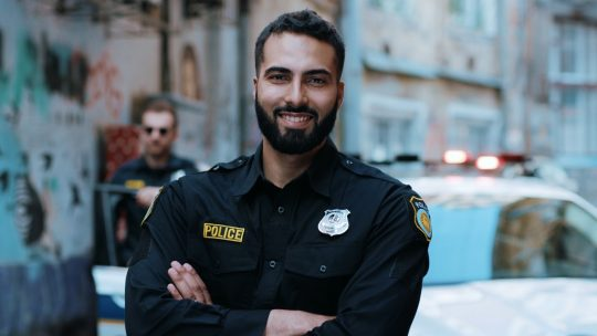 Smiling young man cops stand near patrol car look at camera enforcement happy officer police uniform auto safety security communication control policeman portrait close up slow motion