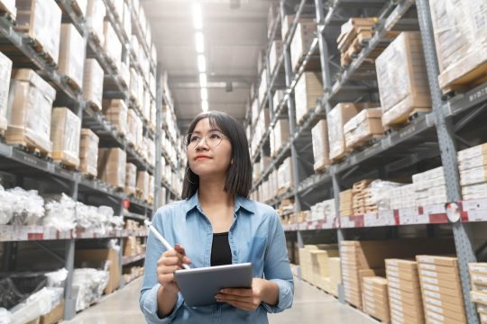 Woman looking in a warehouse, taking inventory of the items on a checklist