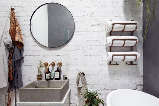 Modern bathroom with white brick wall, concrete sink and a round mirror