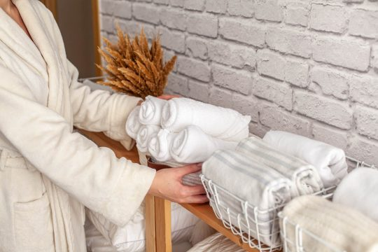 Woman grabbing some towels from an organized bathroom shelf