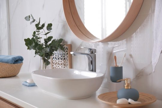 Close up of a bathroom vanity with eucalyptus plant, round mirror and blue stone soap dispenser and toothbrush holder