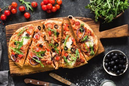 Supreme pizza on cutting board