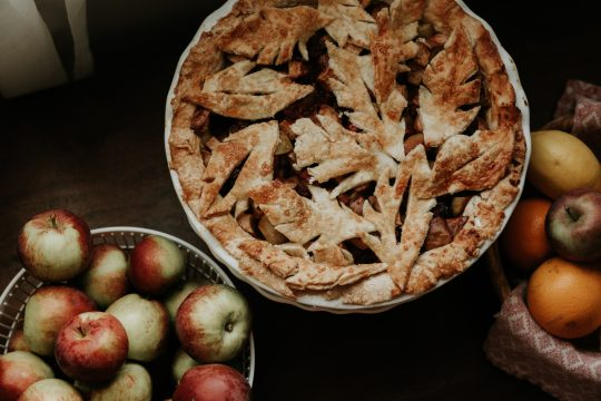 Beautiful apple pie with leaf shaped crust next to a bowl of apples