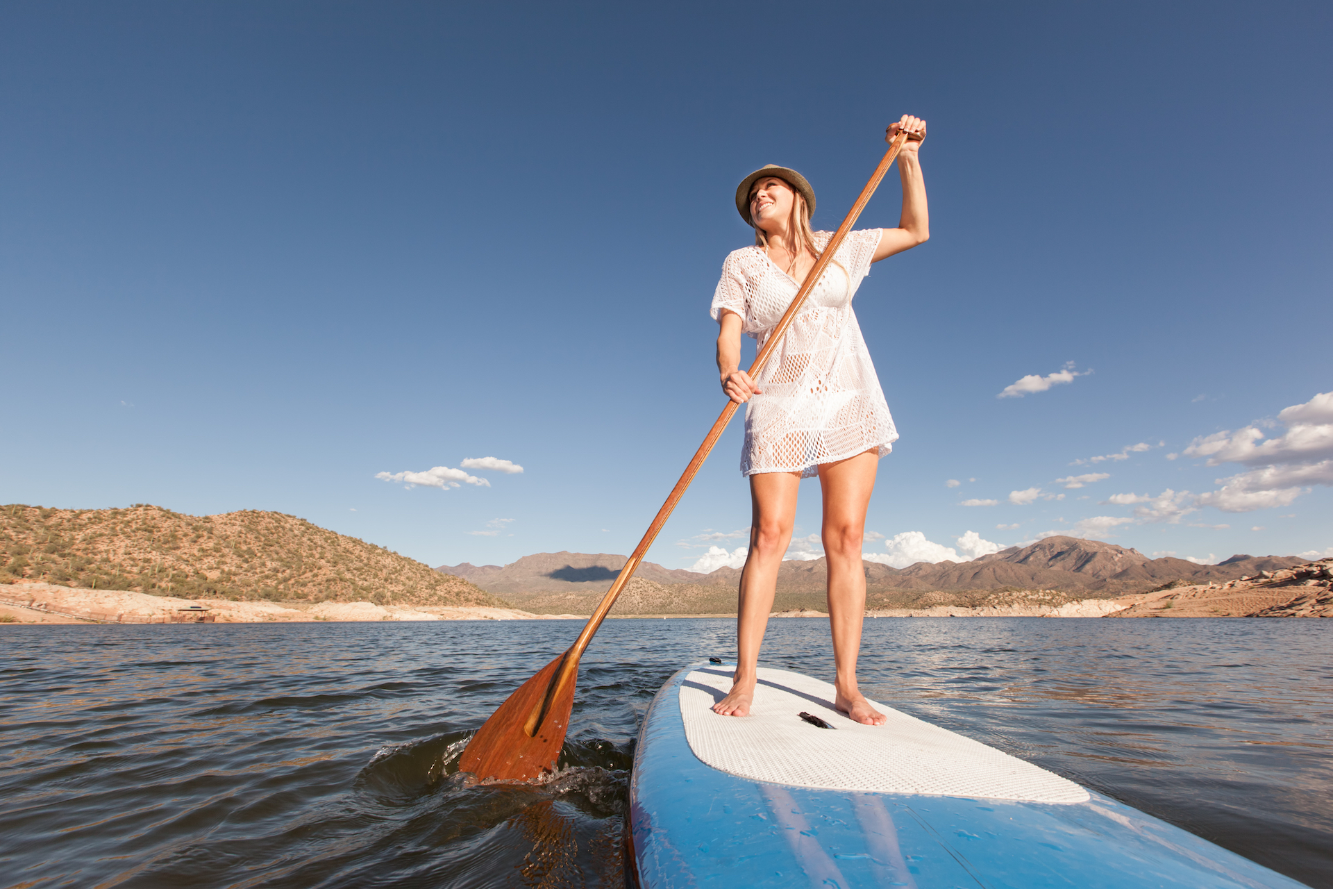 Woman stand up paddle boarding with some mountains in the background