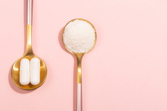 Collagen in powder and pill form with a pink background