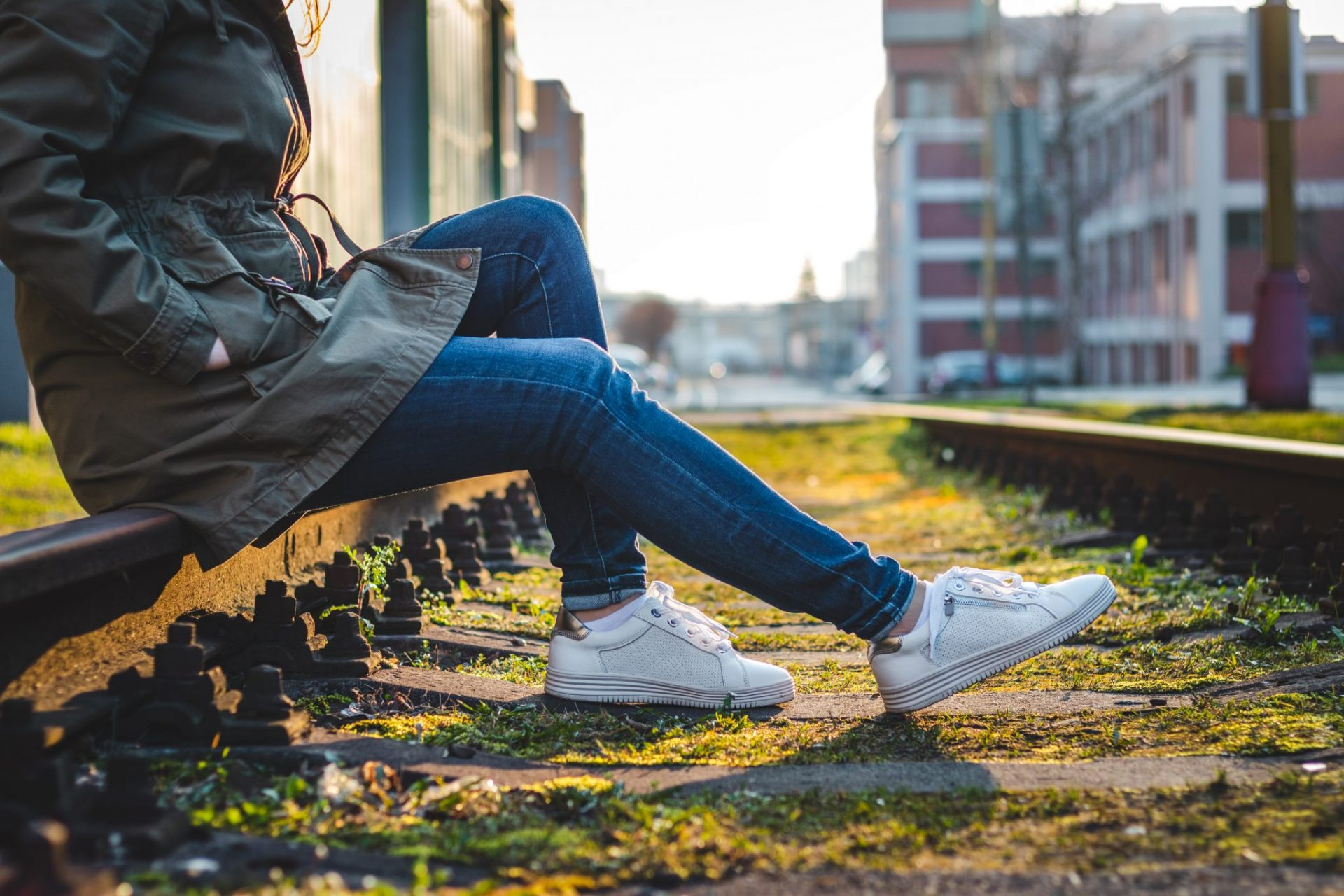 Woman sitting on a moss covered railroad tracks with white sneakers