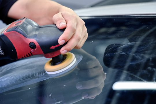 Man polishing his car windshield with Cerium Oxide and a buffer