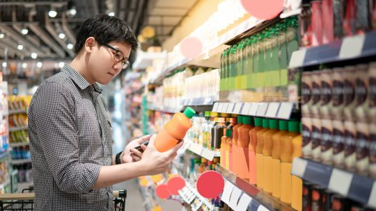 man looking at juice in a grocery store