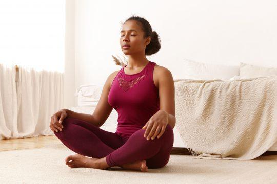 Woman meditating on her bedroom floor