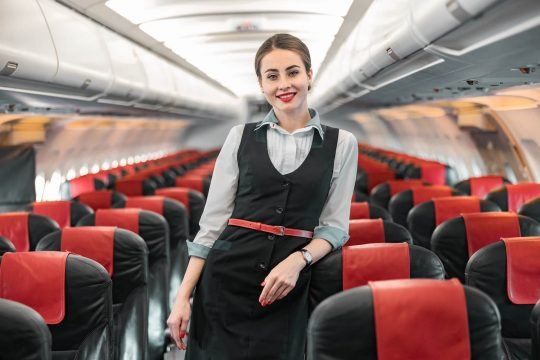 Flight attendant on plane smiling at camera