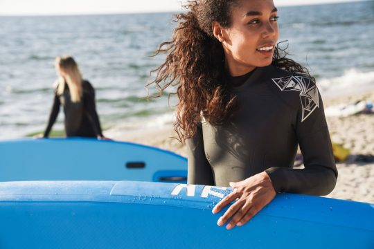Woman in a wet suit holding a paddle board