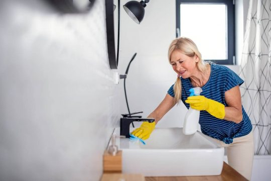 Woman cleaning her bathroom sink