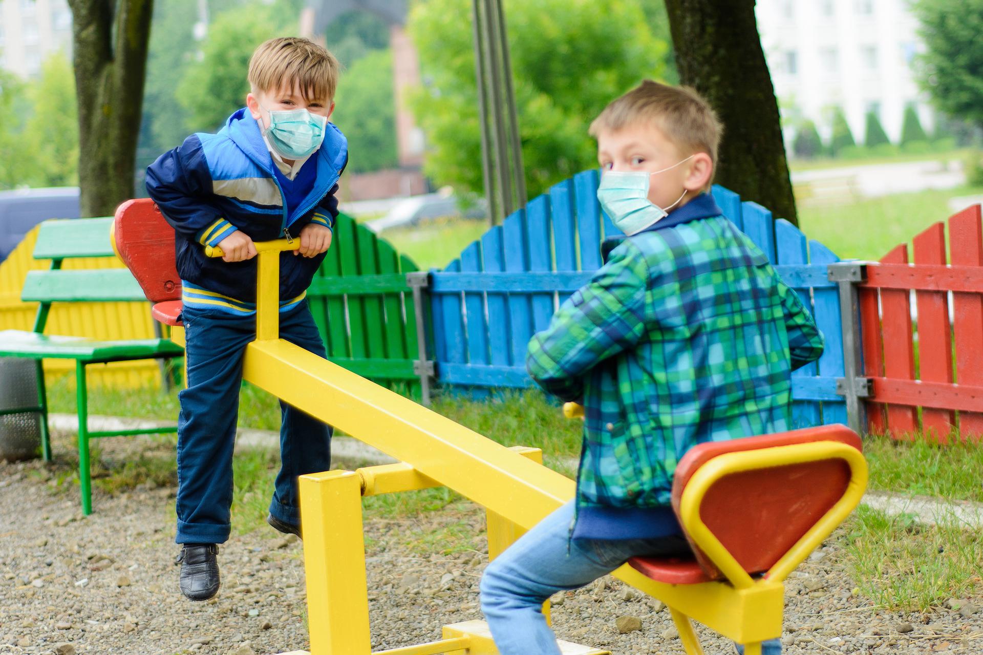 Children school in medical masks play at a quarantine playground